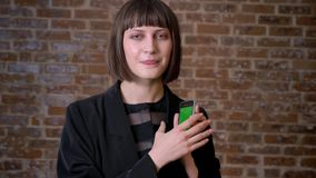 Jeune téléphone heureux de participation de femme avec de chromakey et d'apparence des pouces, fond de mur de briques banque de vidéos