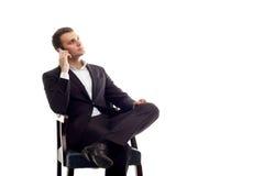 Jeune téléphone parlant se reposant d'homme d'affaires sur le blanc Photos stock
