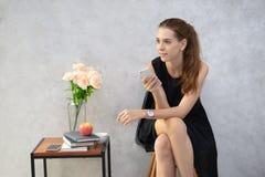 Jeune téléphone portable de participation de femme d'affaires et regarder loin le bureau moderne photographie stock
