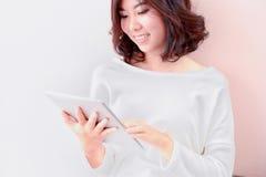 Jeune tablette asiatique d'utilisation de femme de sourire photographie stock libre de droits