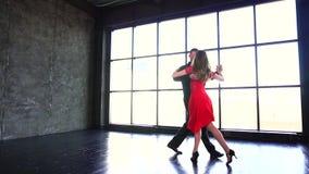 Jeune tango sexy de danse de couples Fille professionnelle dans le latin de danse rouge de robe et d'homme Un studio moderne banque de vidéos