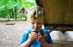 Jeune tasse blonde de boissons de garçon de thé - humide, malpropre, sale, souillé et heureux Photographie stock libre de droits