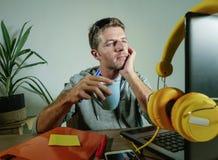 Jeune tasse de café potable d'affaires de bureau heureux et attrayant d'homme à la maison semblant travail satisfait et sûr avec  photo stock