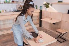 Jeune tasse de portion de barman d'afro-américain de café à une table photos libres de droits