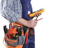 Jeune technicien d'électricien dans les vêtements et des outils de travail d'isolement photo stock
