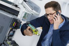 Jeune technicien masculin r?parant la machine num?rique de photocopieur photos libres de droits