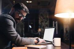 Jeune texte de dactylographie de chef de projet sur l'ordinateur portable au bureau de nuit Homme barbu d'affaires travaillant au Images stock