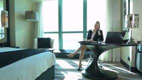 Jeune thé potable blond sexy de femme d'affaires dans la chambre d'hôtel ou le bureau Voyage d'affaires La belle dame parle par l banque de vidéos