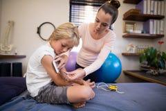 Jeune thérapeute féminin plaçant des électrodes sur le bras du garçon Image stock