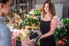 Jeune therminal gai d'argent de prise de fleuriste dans des mains Elle regarde le client Jeune téléphone de prise d'homme d'affai photo libre de droits