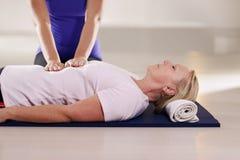 Jeune thérapeute faisant la thérapie de reiki à la femme supérieure Images stock