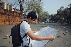 Jeune touriste asiatique avec le sac de sac à dos explorant une carte dans la porte de Tha Phae, Chiang Mai, Thaïlande Images stock