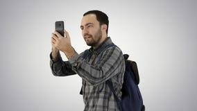 Jeune touriste attirant avec le sac à dos marchant et à l'aide du téléphone portable sur le fond de gradient images libres de droits