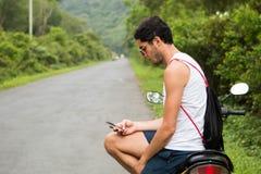 Jeune touriste avec des lunettes de soleil se reposant sur une motocyclette de location vérifiant un smartphone image stock
