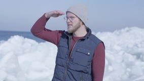 Jeune touriste beau d'homme concentré sur quelque chose près du glacier de chute de neige de glace froide derrière la mer d'hiver banque de vidéos