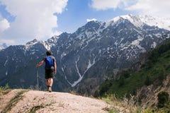 Jeune touriste en montagnes avec un poteau de marche Photographie stock