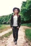 Jeune touriste féminin avec un sac à dos rose et un chapeau en cuir de style de cowboy regardant la distance Portrait concept d'a images stock