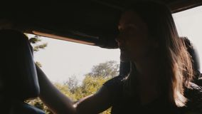 Jeune touriste féminin heureux souriant, appréciant le beau tour en voiture d'excursion de safari le long de forêt sauvage ensole banque de vidéos