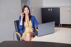 Jeune travail auxiliaire dans le bureau à l'ordinateur portable image libre de droits