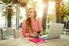 Jeune travail créatif de femme sur l'ordinateur portable tout en prenant le petit déjeuner sur la terrasse Images stock