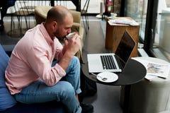 Jeune travail d'étudiant sur le netbook tenant la tasse du thé ou du café tandis qu'il s'asseyant dans le café moderne Images libres de droits