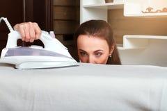 Jeune travail de femme au foyer avec du fer de vapeur photos stock