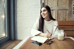 Jeune travail de fille de hippie en café, avec le bloc-notes dans un café près de temps de déjeuner de fenêtre avec du café Images stock