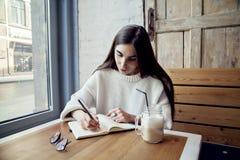 Jeune travail de fille de hippie en café, avec le bloc-notes dans un café près de temps de déjeuner de fenêtre avec du café Photographie stock
