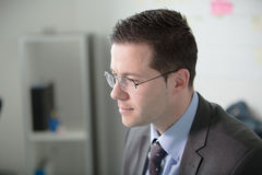 Jeune travail heureux d'homme d'affaires dans le bureau moderne Homme d'affaires bel In Office Vrais bussinesmen d'économiste, pa photographie stock libre de droits