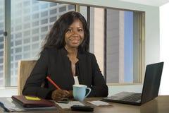 Jeune travailler américain de femme d'affaires d'africain noir heureux et attirant sûr au sourire de bureau d'ordinateur satisfai photos stock