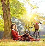 Jeune travailler femelle sur un ordinateur portable posé sur une herbe en parc Image libre de droits