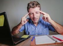 Jeune travailler soumis à une contrainte et accablé fou d'homme malpropre au bureau désespéré avec le mal de tête et les depres d photos libres de droits