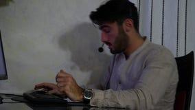 Jeune travailleur à la maison de sexe masculin avec le casque clips vidéos