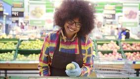 Jeune travailleur africain de magasin de femme avec une coiffure Afro regardant la caméra et le sourire banque de vidéos