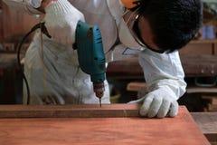 Jeune travailleur asiatique avec la sécurité fonctionnant le foret électrique sur le conseil en bois dans l'atelier de menuiserie image stock