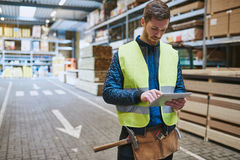 Jeune travailleur d'entrepôt consultant un comprimé Image stock