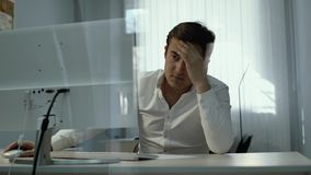Jeune travailleur d'homme de bureau s'asseyant avec des mains sur la tête devant l'ordinateur banque de vidéos
