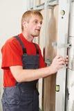 Jeune travailleur d'homme de charpentier avec le niveau Image stock