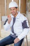 Jeune travailleur de la construction beau mangeant la pomme rouge sur le site images stock