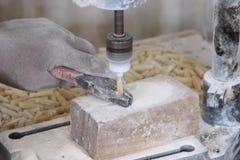 Jeune travailleur de sexe masculin africain à une usine de souvenir fonctionnant avec une machine photo stock