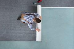 Jeune travailleur de sexe masculin dans des de façon générale roulant le tapis images stock