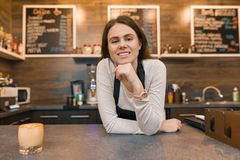 Jeune travailleur féminin de café de barman souriant regardant la caméra avec des bras pliés croisés près du compteur de barre photographie stock libre de droits
