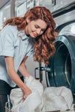jeune travailleur féminin de nettoyage à sec prenant des vêtements hors de photographie stock libre de droits