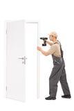 Jeune travailleur installant une porte photographie stock