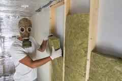 Jeune travailleur musculaire dans le personnel isolant de laine de roche de masque de gaz dans le cadre en bois pour de futurs mu photo stock