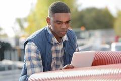 Jeune travailleur regardant le comprimé dans la cour de matériaux photos libres de droits