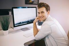 Jeune travailleur s'asseyant dans un bureau à l'ordinateur Indépendant dans une chemise blanche Le concepteur s'assied devant la  Image libre de droits