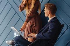 Jeune type élégant avec l'ordinateur portable et la fille avec le téléphone ensemble, jeune homme d'affaires, travail d'indépenda photos libres de droits