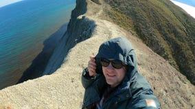 Jeune type élégant dans le capot Supports sur le cap Autour de la mer Apprécie le voyage et le mode de vie actif clips vidéos