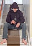 Jeune type adolescent s'asseyant sur les escaliers buvant l'alcool photo libre de droits